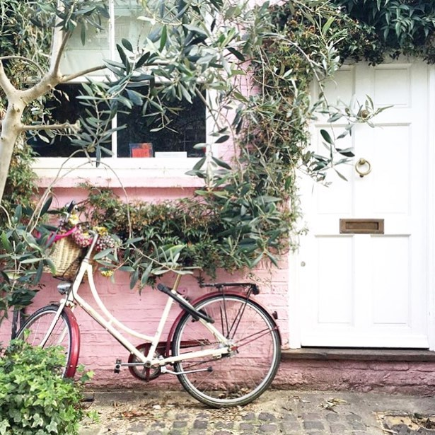 A pretty door with a cute bike and pink wall always gets noticed
